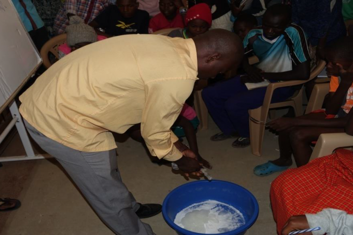 Youth being skilled to make liquid soap.
